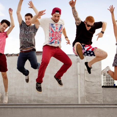 Group Of Friends Jumping Of Beam On Rooftop